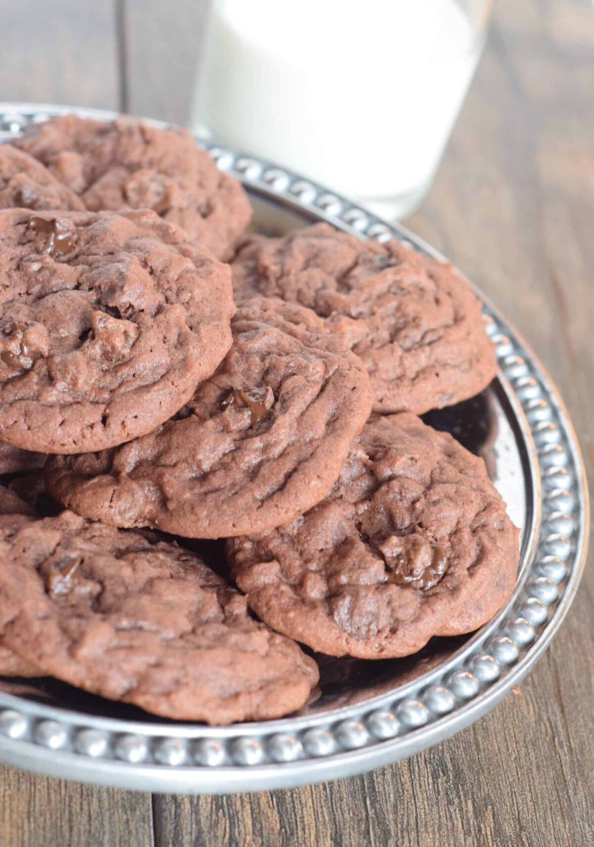 Chocolate cookies with chocolate chips. Plate of them and glass of milk