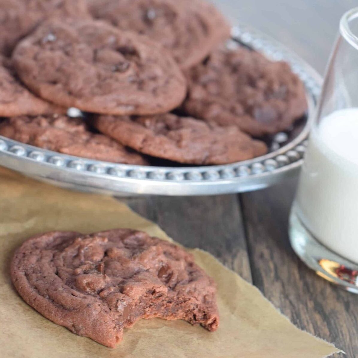 Chocolate cookies with chocolate chips with bite out of one on parchment. Plate of them behind it and glass of milk