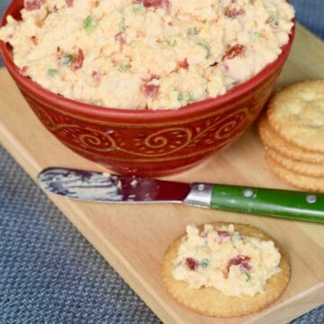 Red bowl of jalapeno pimento cheese on wooden cutting board. Green spreading knife and cracker with pimento cheese spread on it placed on cutting board.