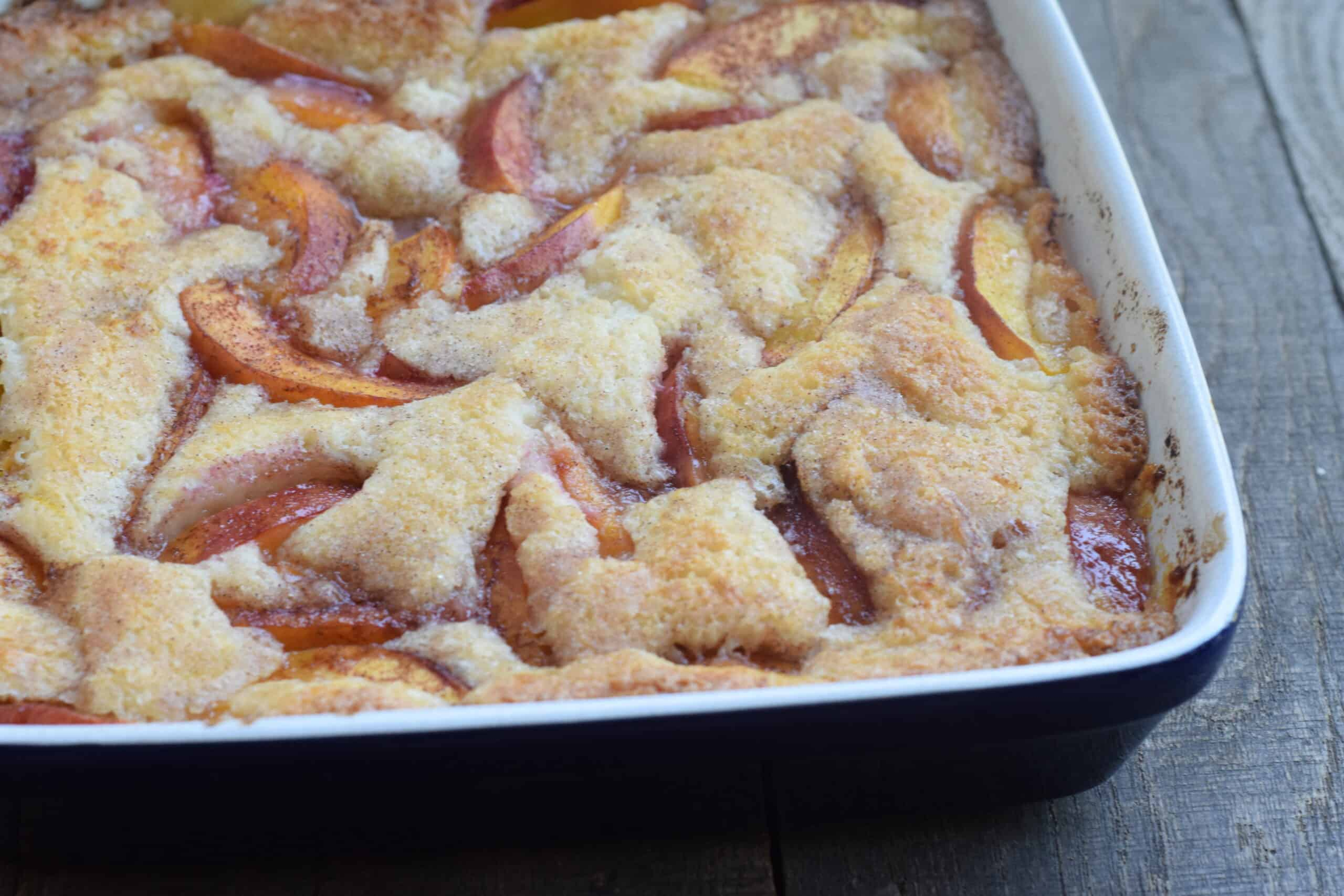 Nectarine cobbler in blue square dish on wooden surface