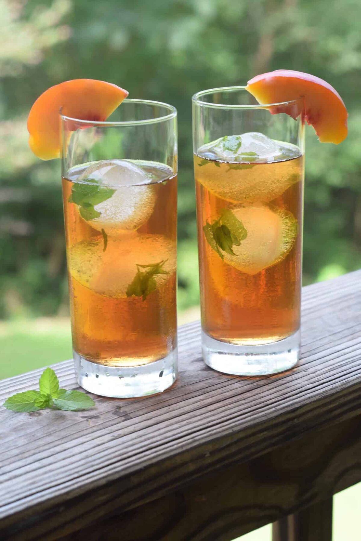 2 glasses of peach tea with mint ice cubes garnished with peach wedges sitting on a wooden railing