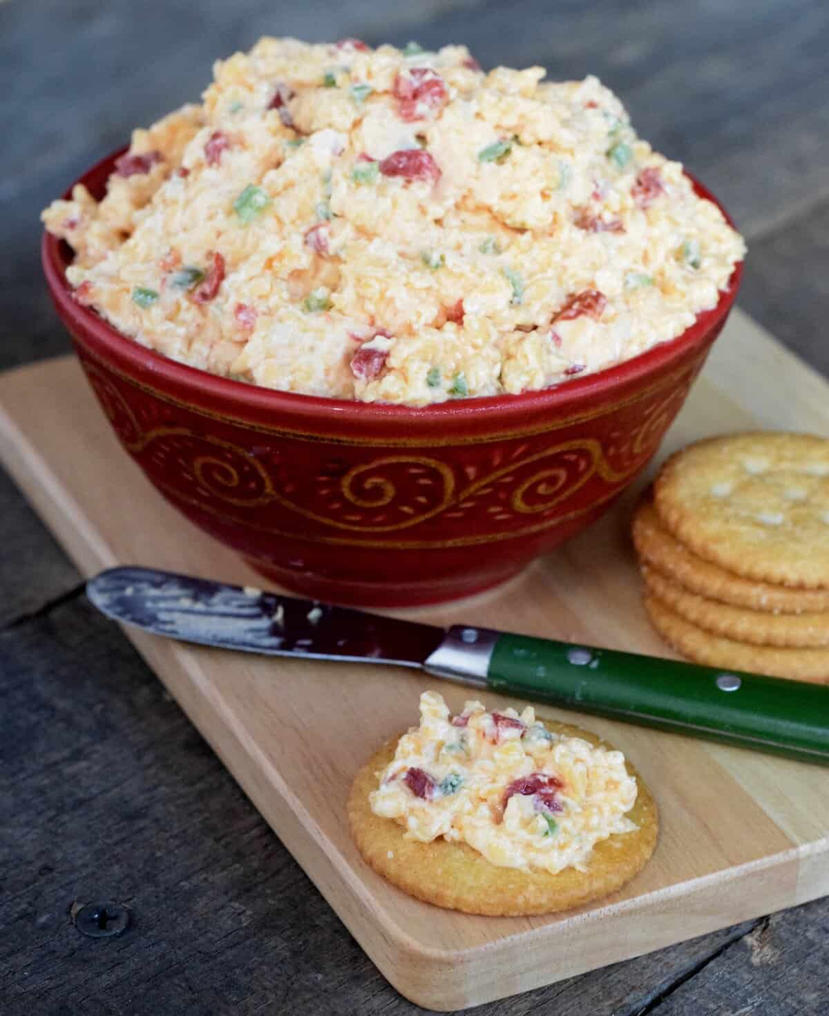 Red bowl of white pimento cheese with flecks of red and green on a wooden cutting board