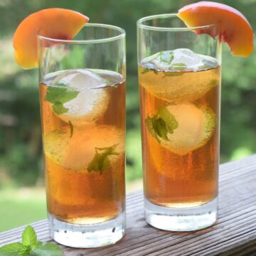 two tall glasses of tea over round mint ice cubes and garnished with peach slices