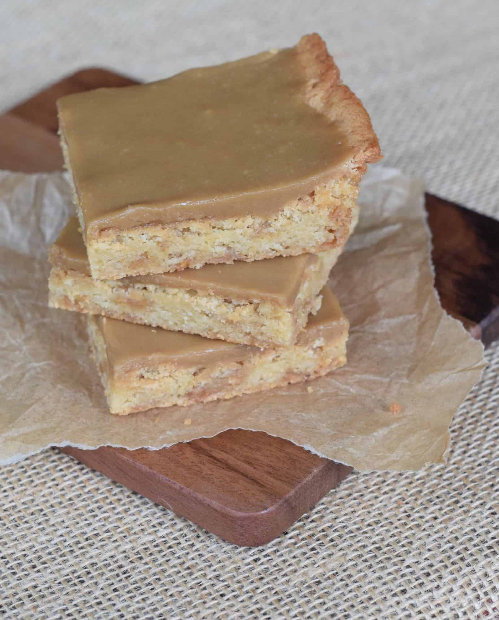 A stack of 3 Toffee Blonde Brownies with Cheaters Caramel icing placed on a dark brown cutting board.