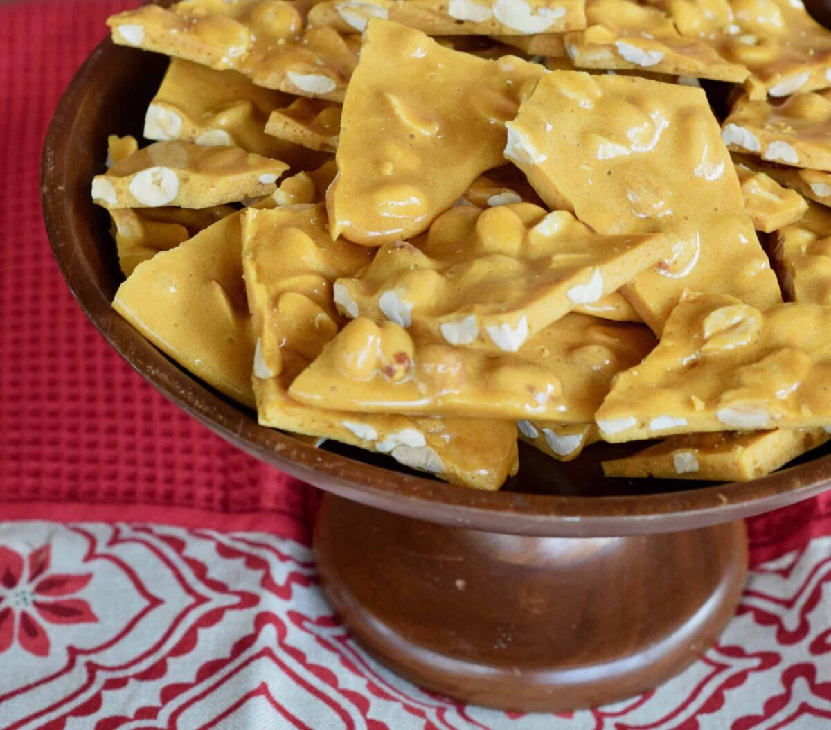 Peanut Brittle in a wooden cake stand on red poinsettia cloth.