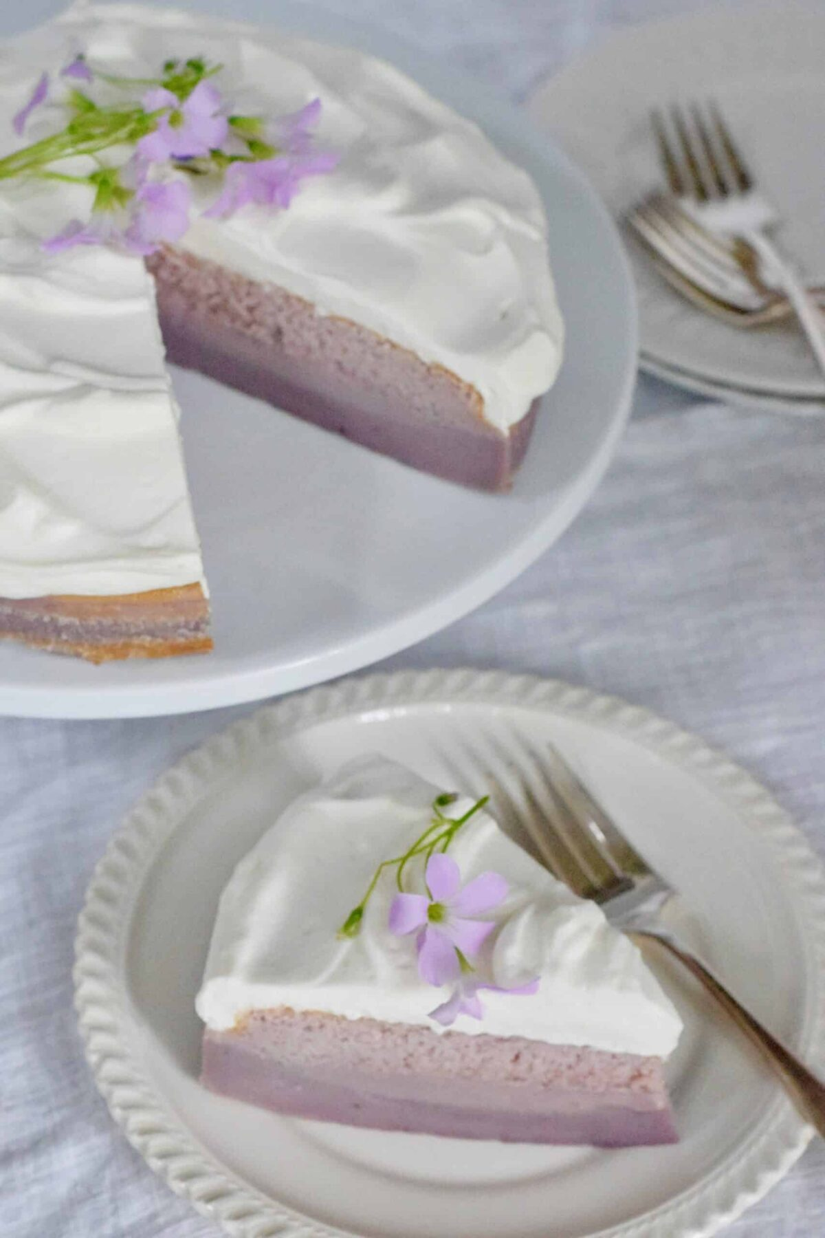 Purple Sweet potato Magic Cake with a slice cut and placed on a white plate with forks on a white tablecloth. Garnished with purple oxalis
