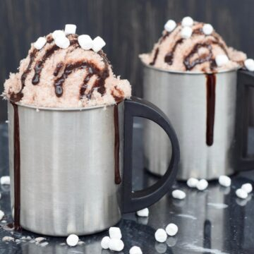Two silver mugs of chocolate snow ice cream with chocolate syrup drizzled down the side and marshmallows on a black surface