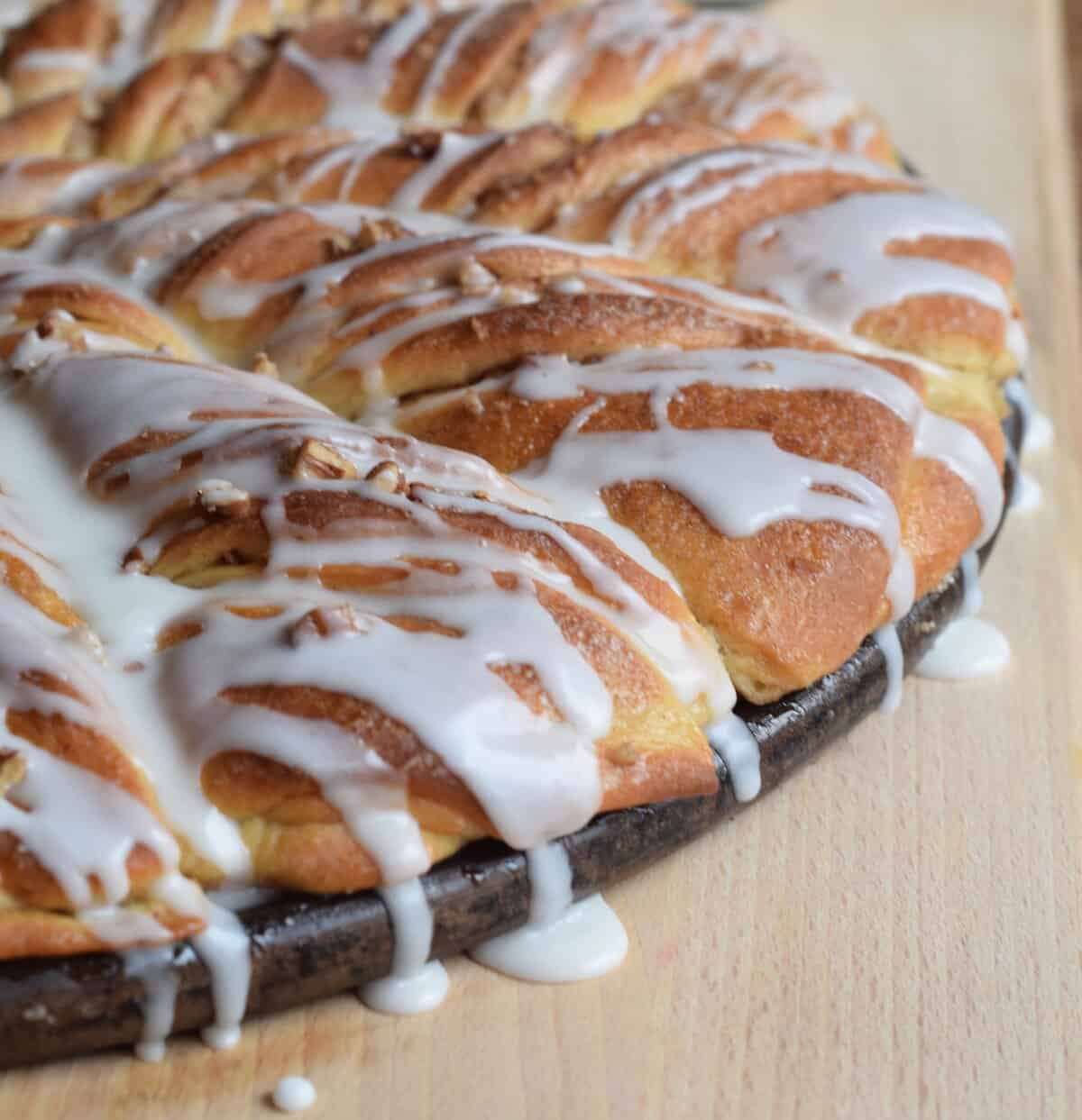 twisted sweet rolls with icing dripping over the side of round pan