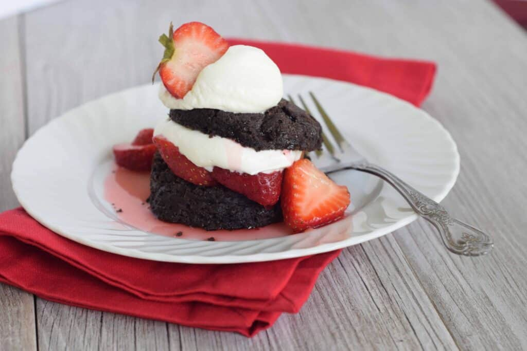 Chocolate Biscuit Strawberry Shortcake by GritsAndGouda.com served on a white plate on a red napkin with a fork on plate.