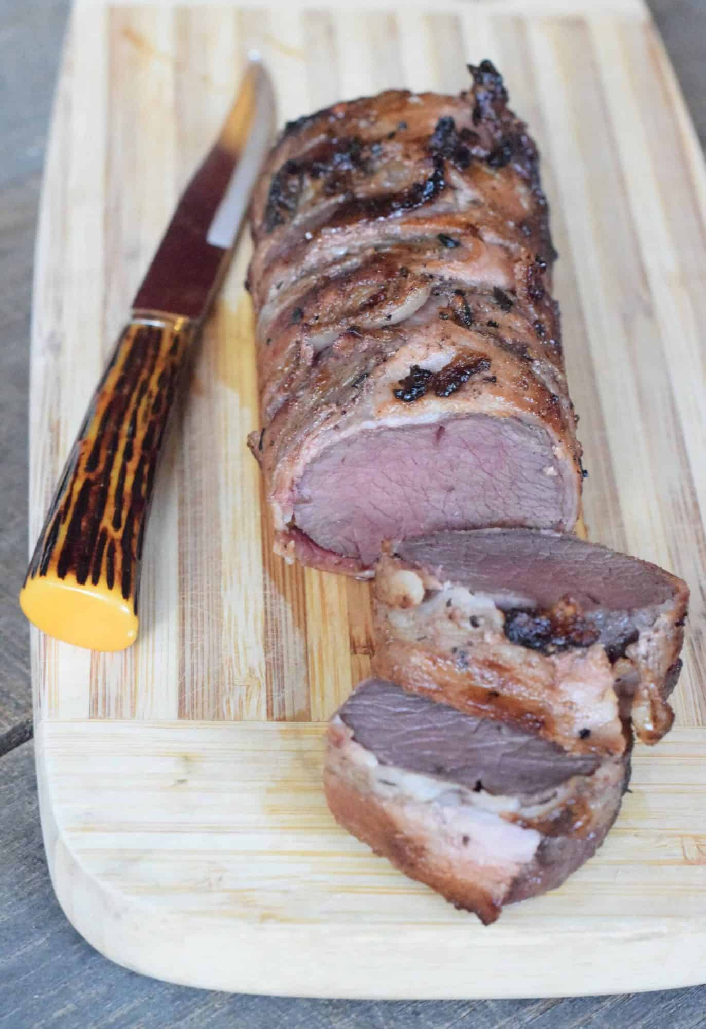 Slices of bacon-wrapped venison backstrap roast on a wooden cutting board and a rustic knife.