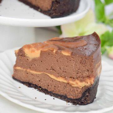 Chocolate-Peanut Butter Swirl Cheesecake slice. whole cheesecake behind it