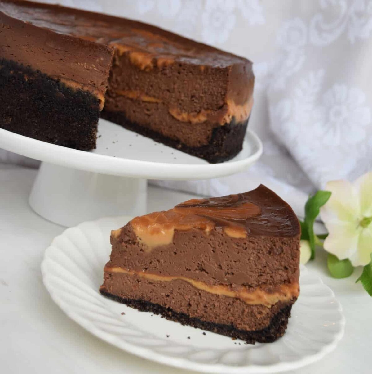slice of chocolate cheesecake on a white plate with the rest of the cake on a cake stand