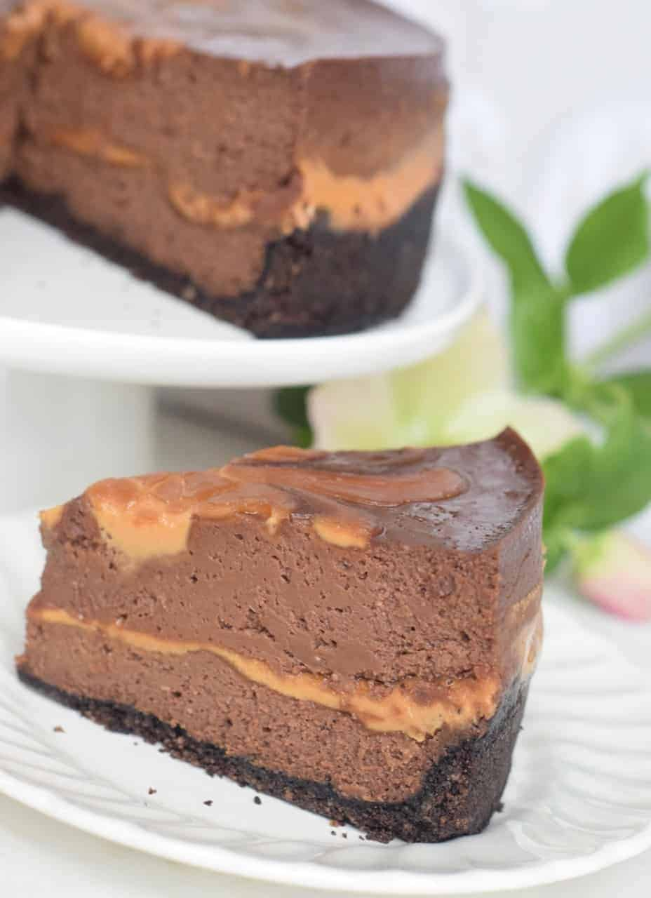 Instant Pot Choc PB Swirl Cheesecake slice on a plate with whole cheesecake on a white cake plate