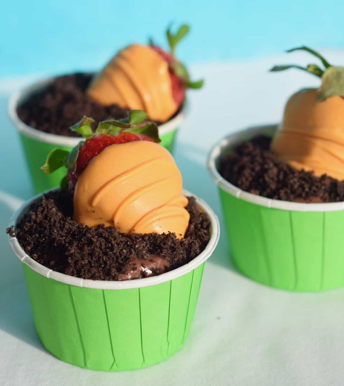 Orange candy coating fresh strawberries as carrots nestled in chocolate pudding and Oreos