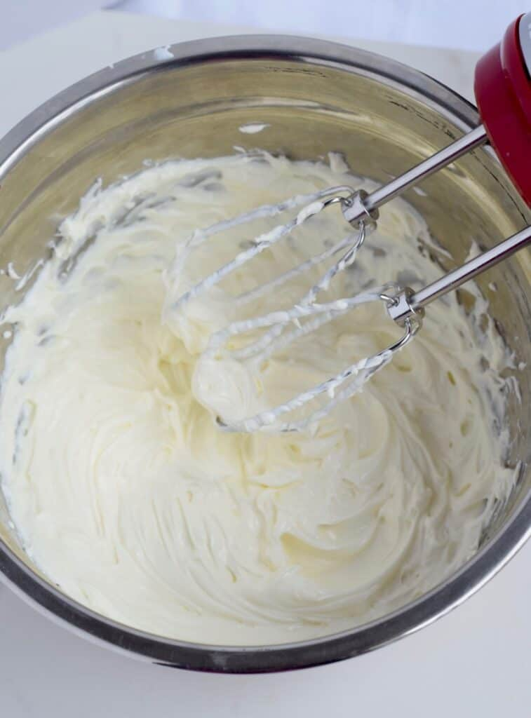 Beat 2 packages softened cream cheese with a mixer until creamy.