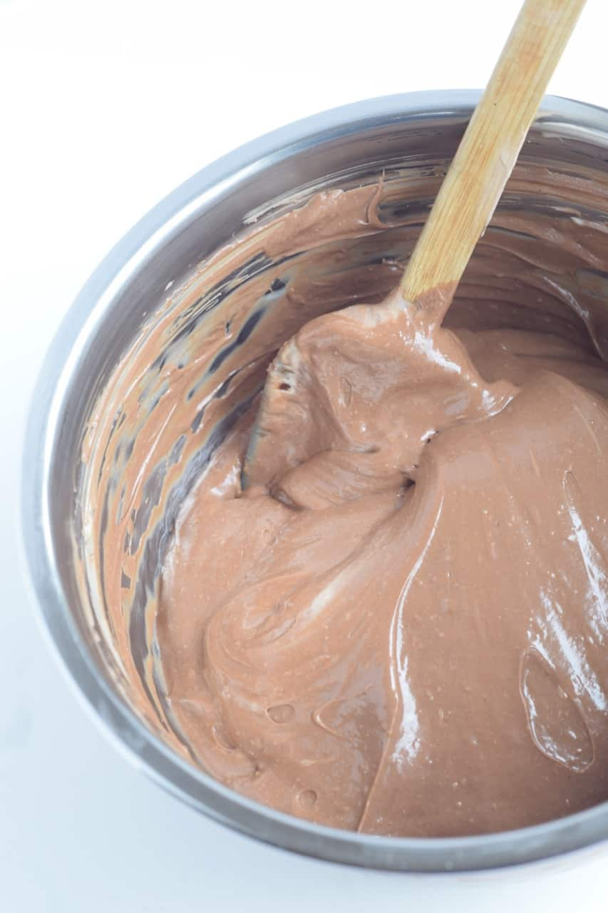 chocolate cheesecake batter in a mixing bowl with spatula