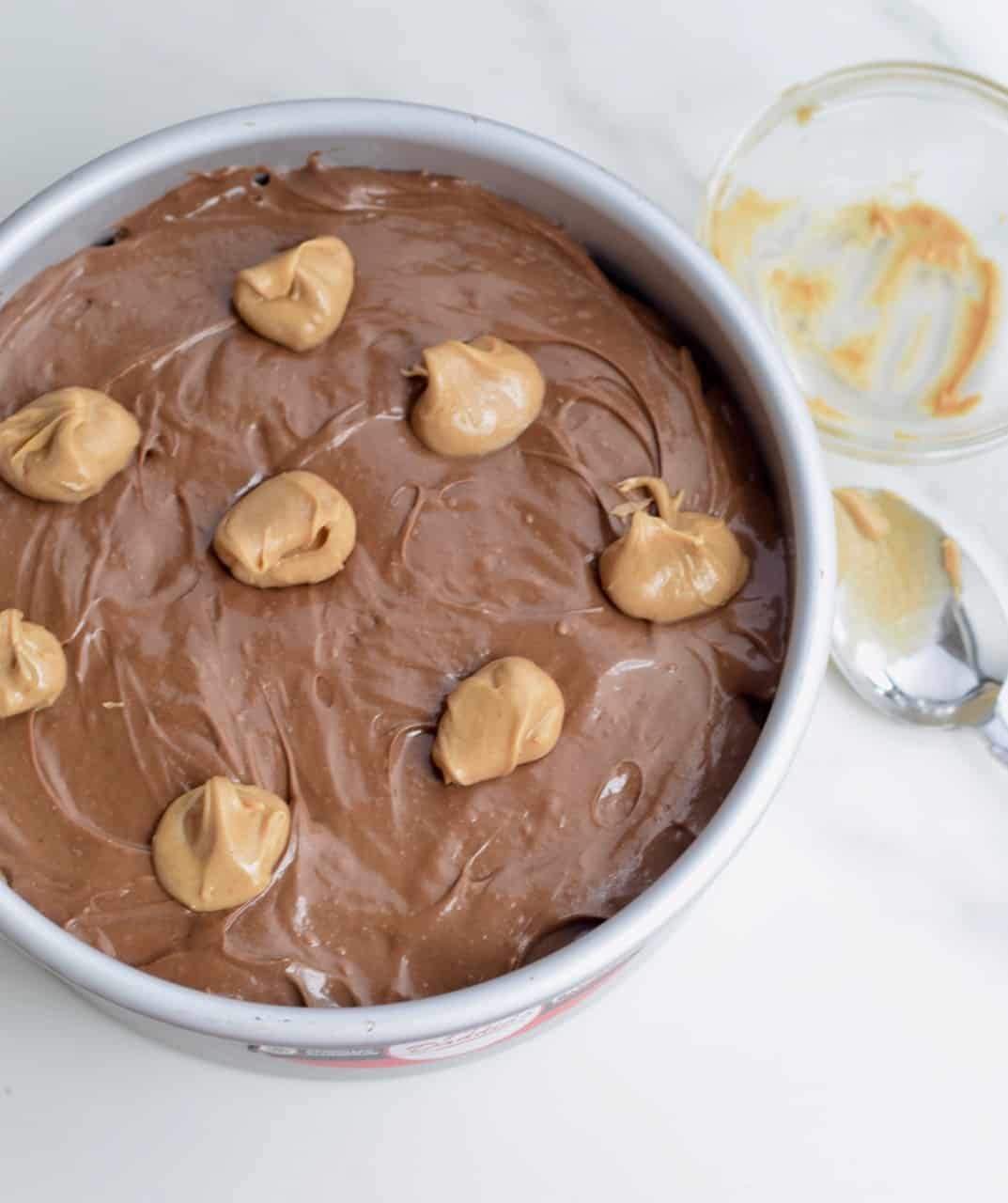 Tiny dollops of peanut butter dolloped on top of chocolate cheesecake batter in a cake pan; spoon with peanut butter on it on surface
