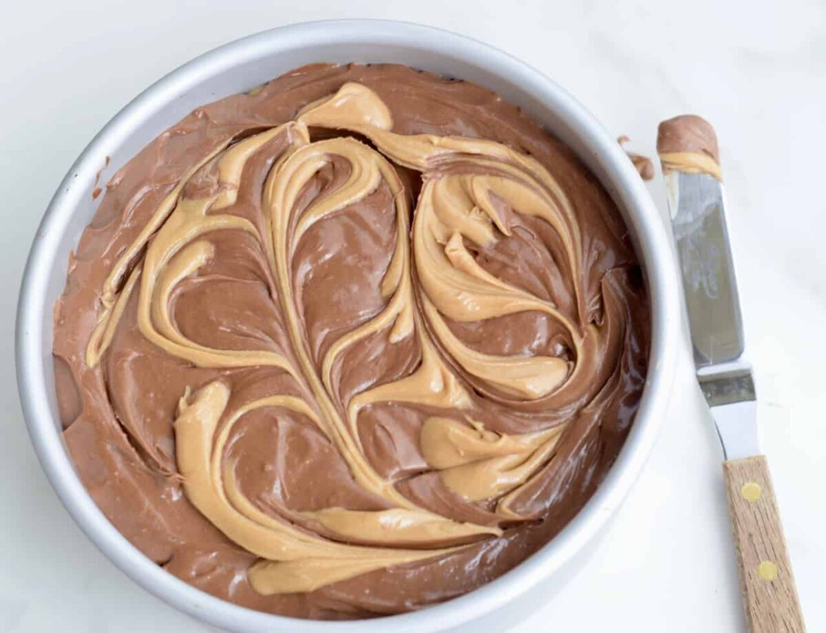 Peanut butter swirled through the top of chocolate cheesecake batter in a cake pan; spreader on surface with peanut butter on the tip.
