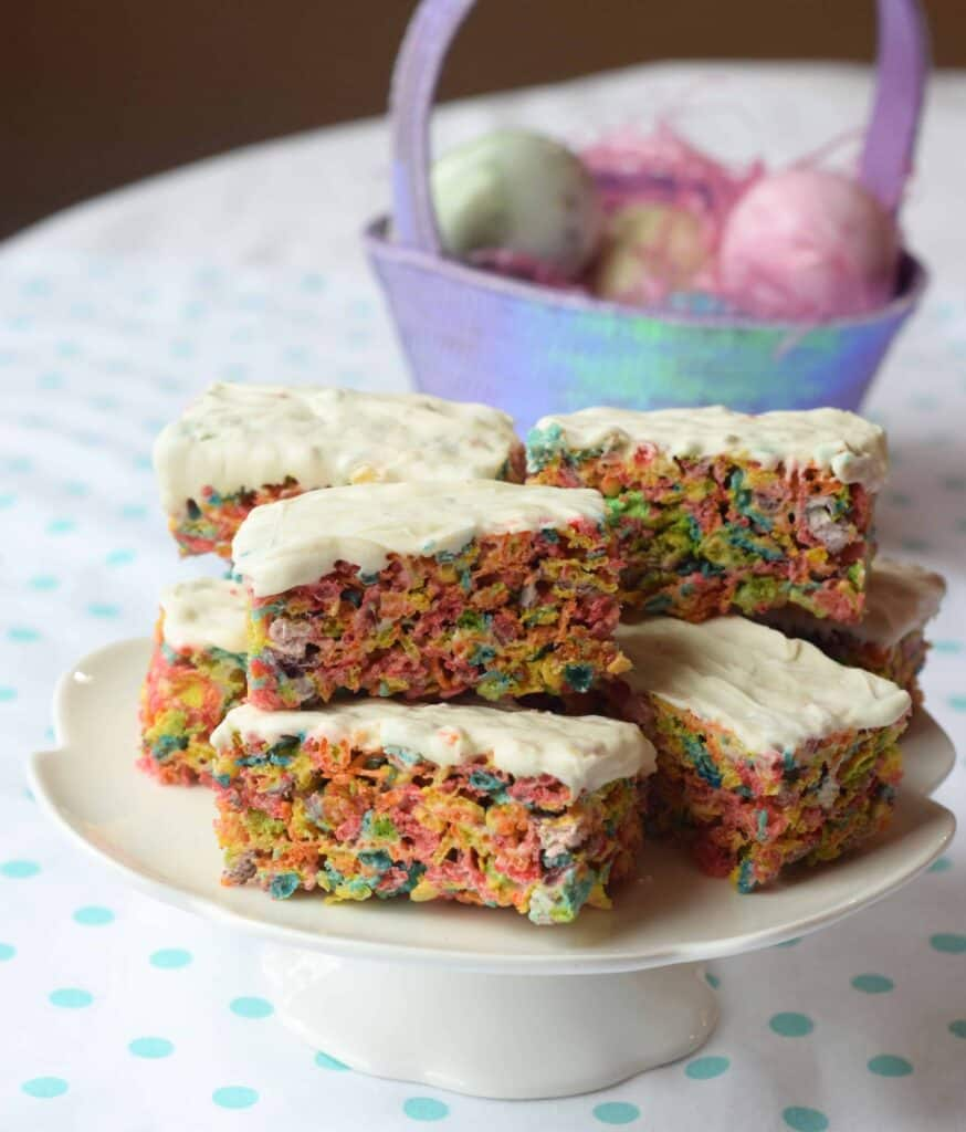 Fruity Pebbles make the perfect pastel fruit-flavored treat for Easter or a Spring shower! They will remind you of Rice Krispy treats. An Easter basket in the background and white cake pedestal on aqua polka dot cloth.