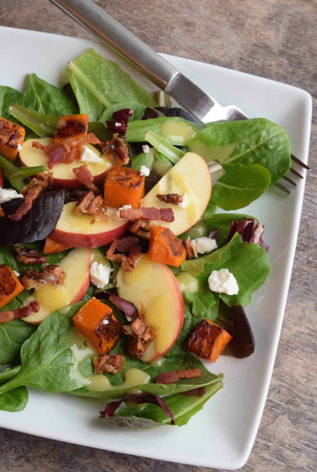 apple butternut salad on a white plate with fork
