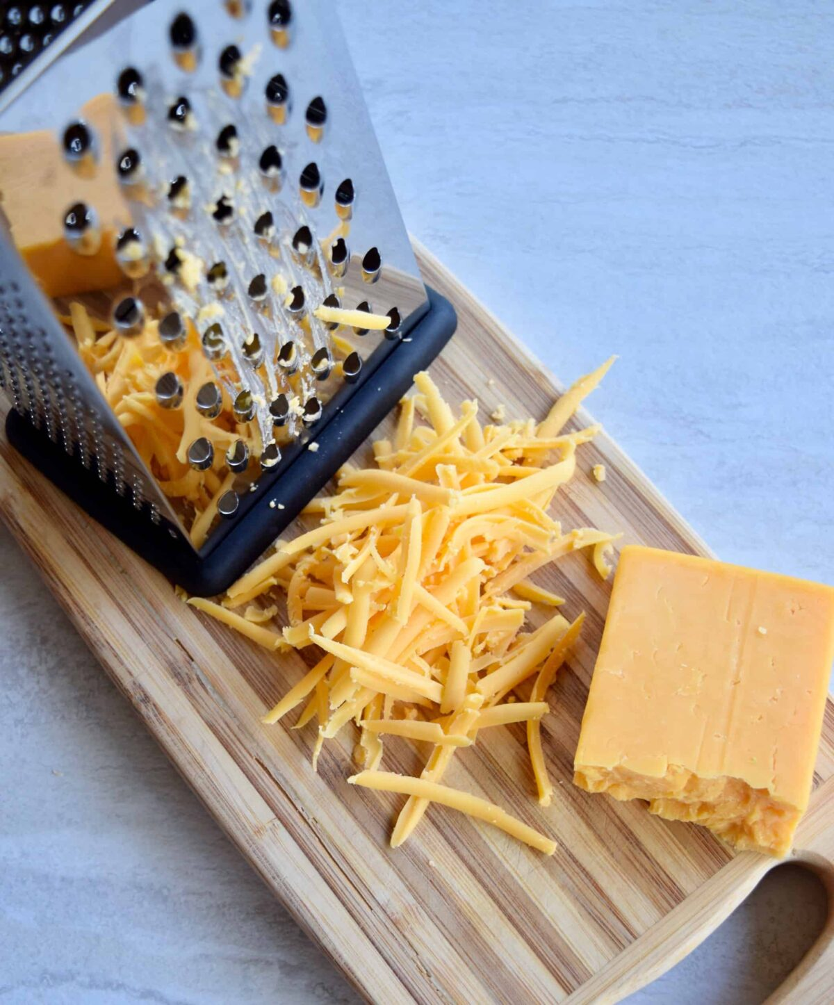 cheese grater with shredded cheddar on a cutting board