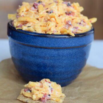 pimento cheese in blue crock with some on a cracker on parchment paper