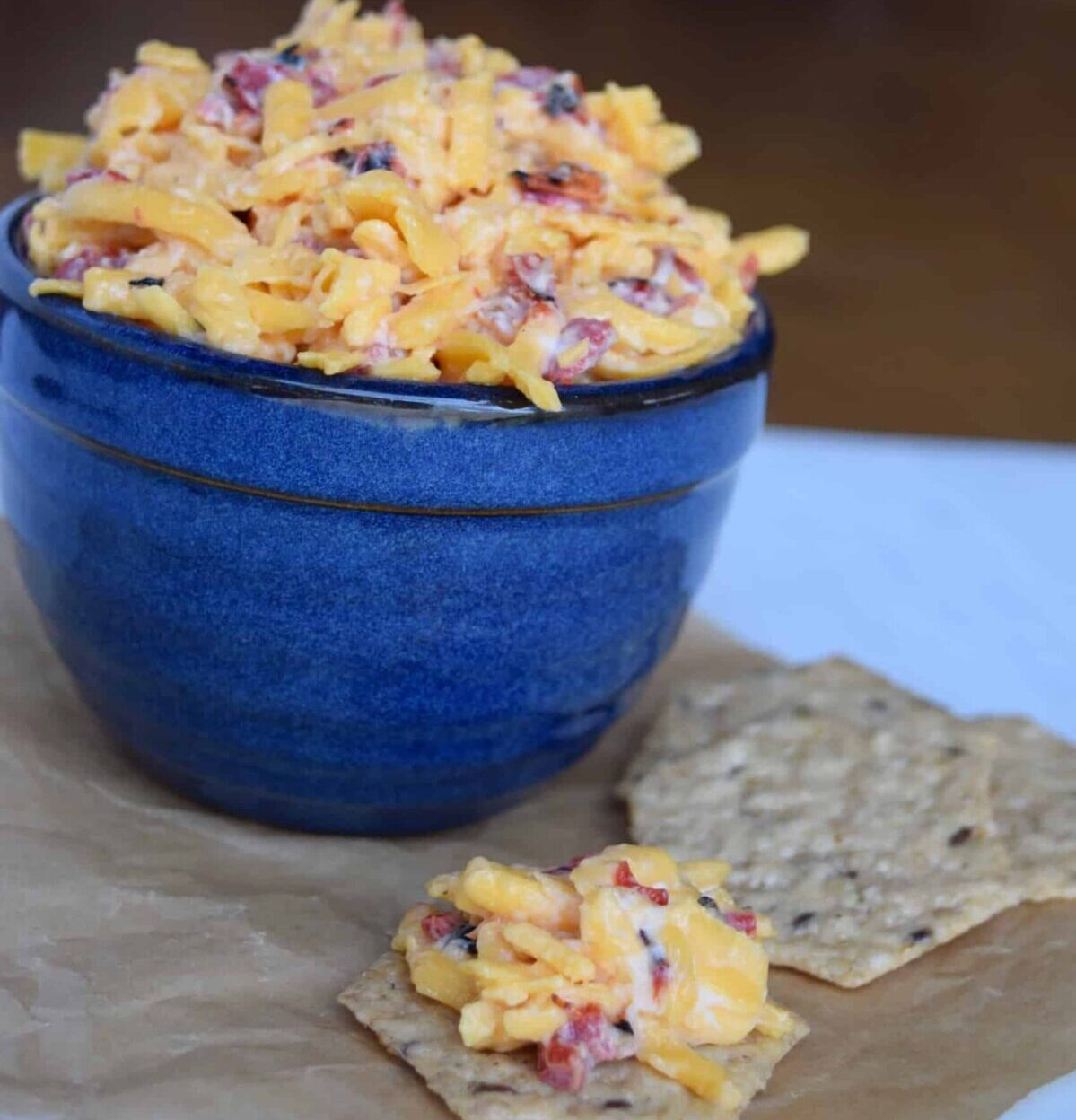 pimento cheese in a blue crock with some on a cracker on brown parchment