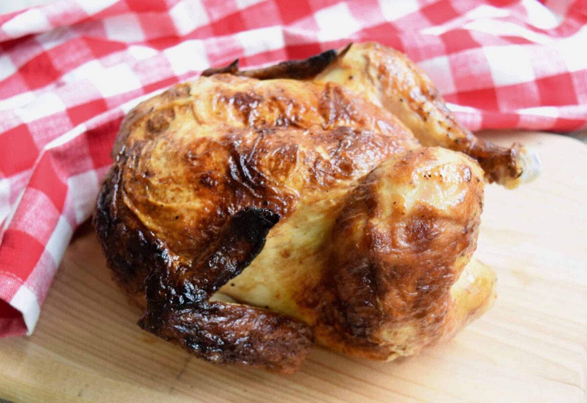 rotisserie chicken on wooden surface next to red white checked cloth