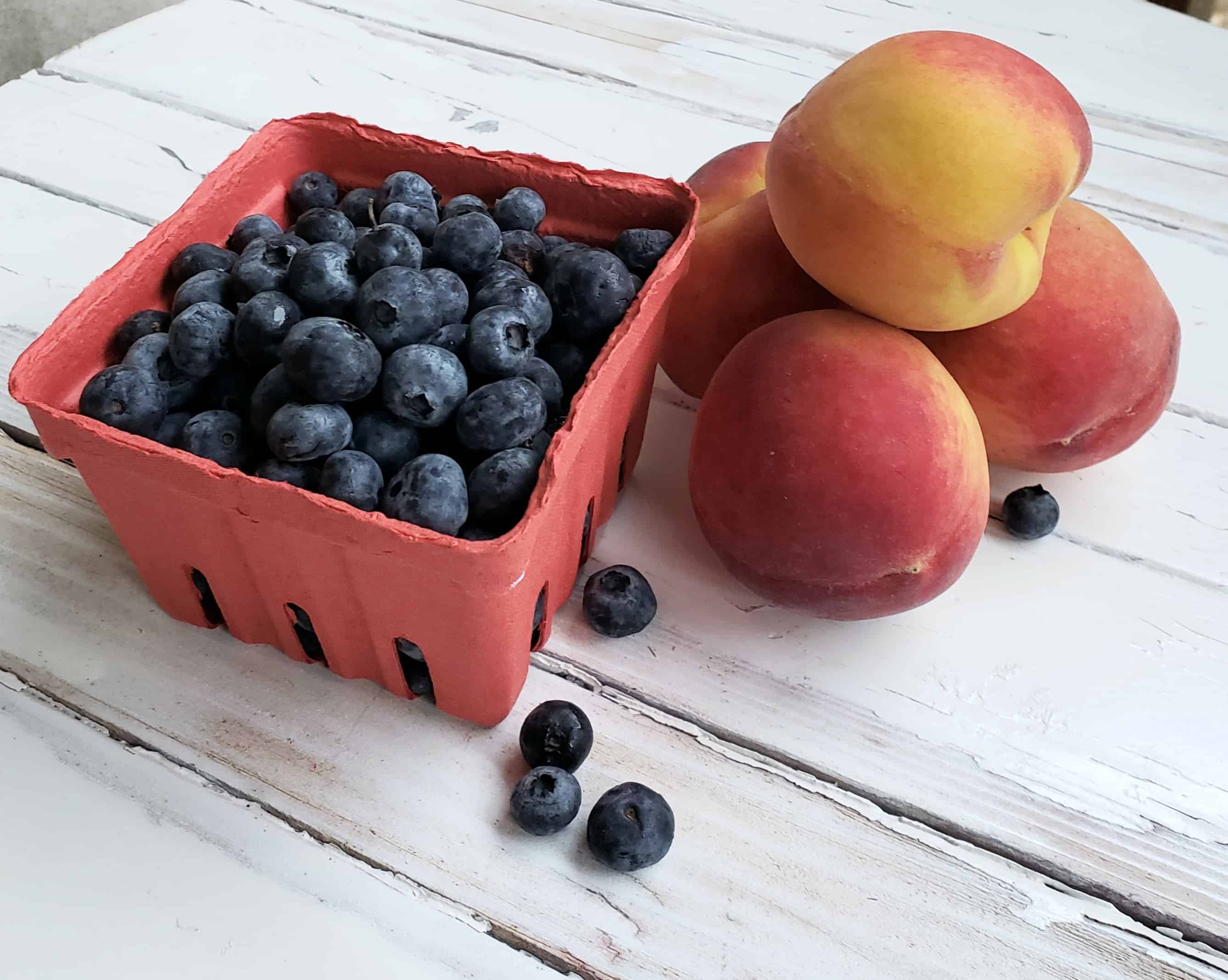 Blueberries and Peaches on white table
