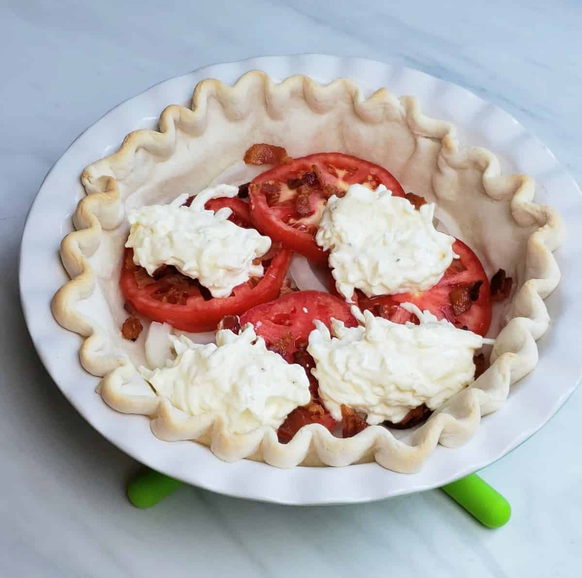 sliced tomatoes, cheese filling layered in a prebaked pie crust sitting on green silicone trivets