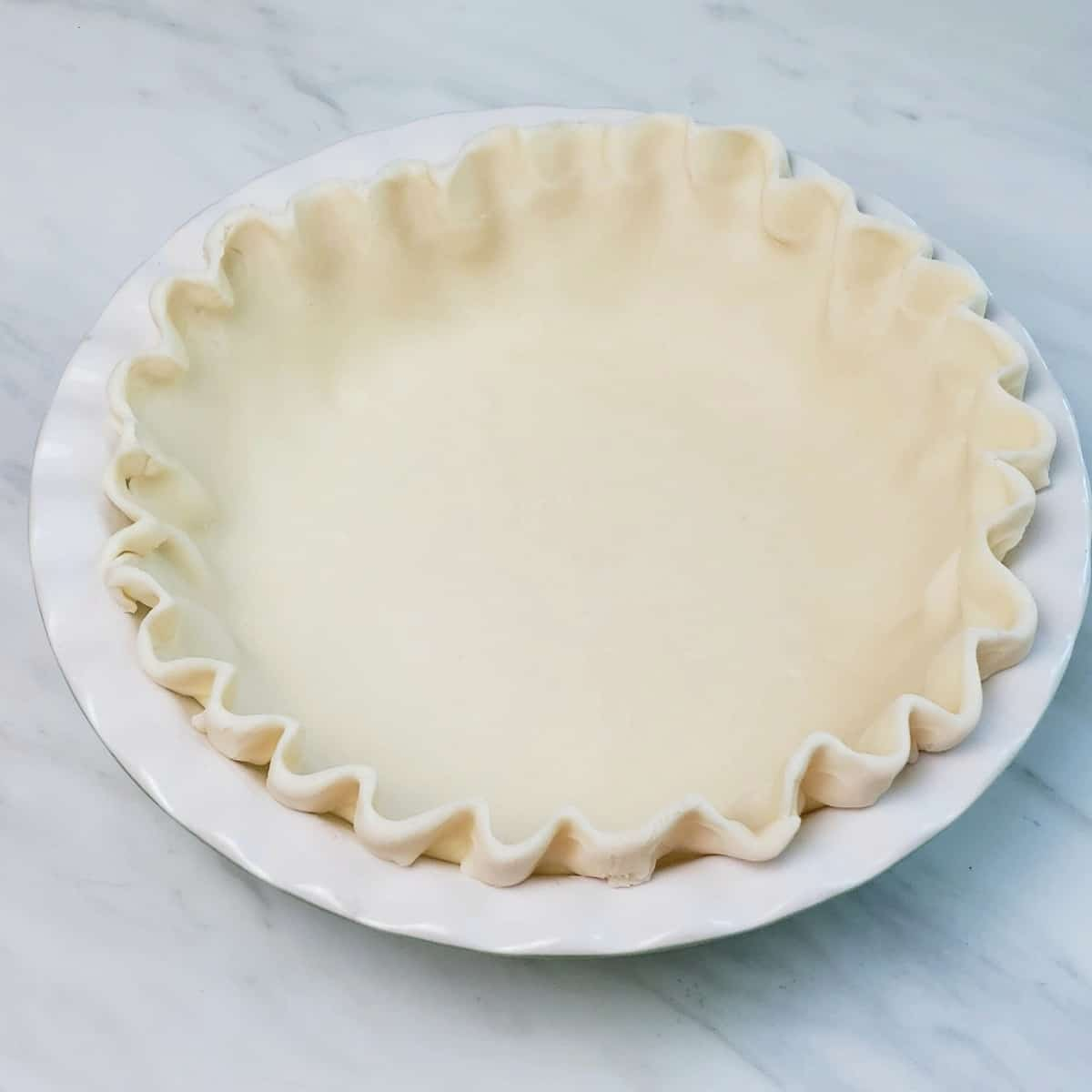 unbaked pie crust fluted in a white pie plate on a marble surface
