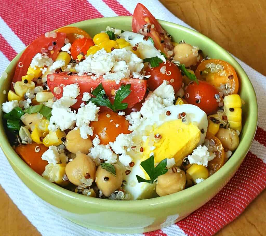 Tri Color Quinoa Salad is packed with protein and bursting with color and flavor. quinoa salad with grape tomatoes boiled egg and chick peas in a green bowl on a red and white napkin with feta