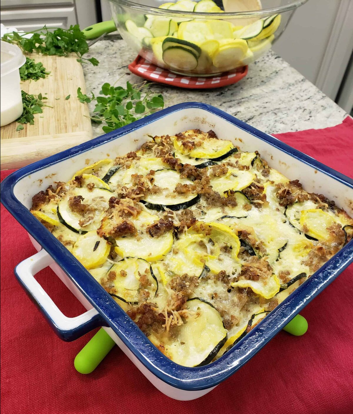 Sausage squash casserole in blue rimmed square casserole on green silicone trivet. Chopped herbs in background