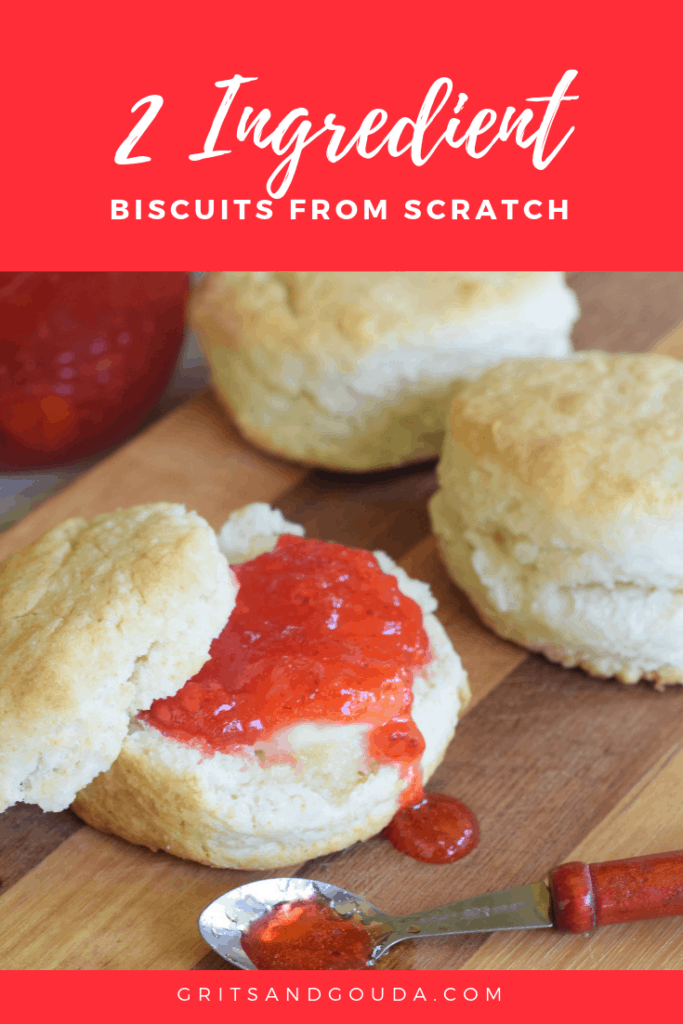 3 biscuits on a wooden cutting board spread with butter and strawberry jam. Tiny spoonful of jam on a spoon spilling out.