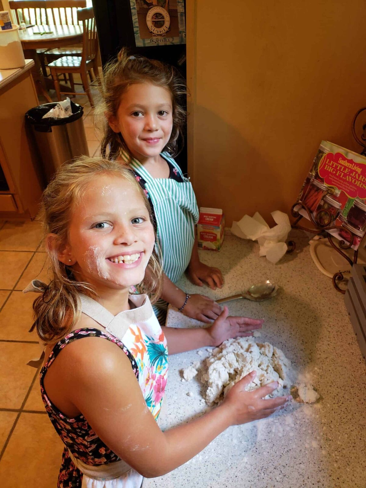 Two girls pressing together biscuit dough on countertop