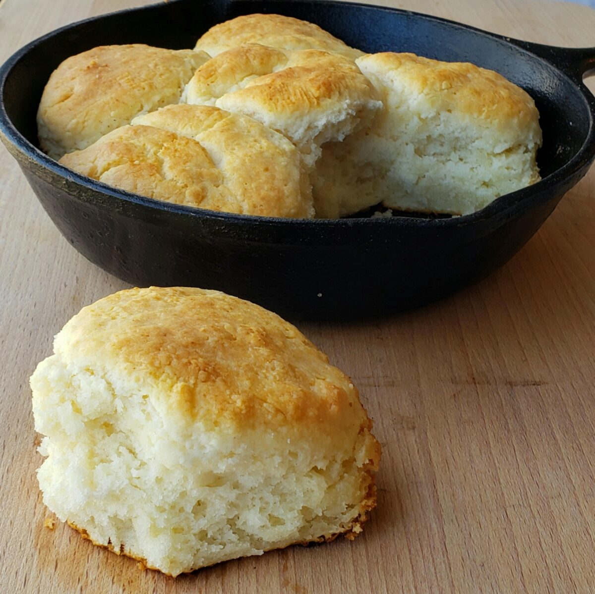small cast iron skillet with biscuits; one biscuit on wooden surface