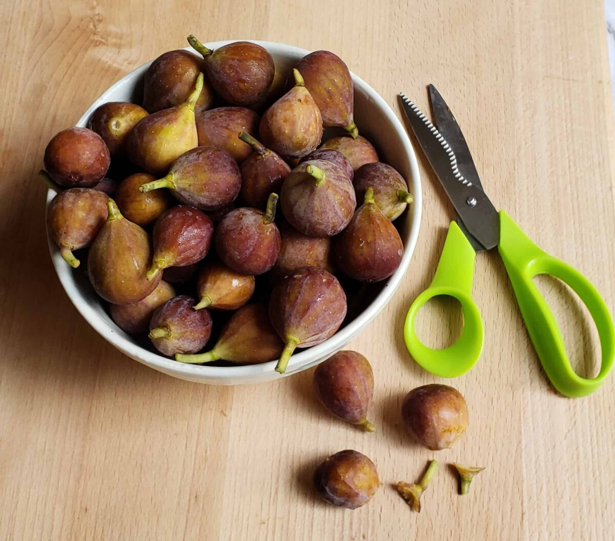 Bowl of small mission figs with stems snipped off with scissors