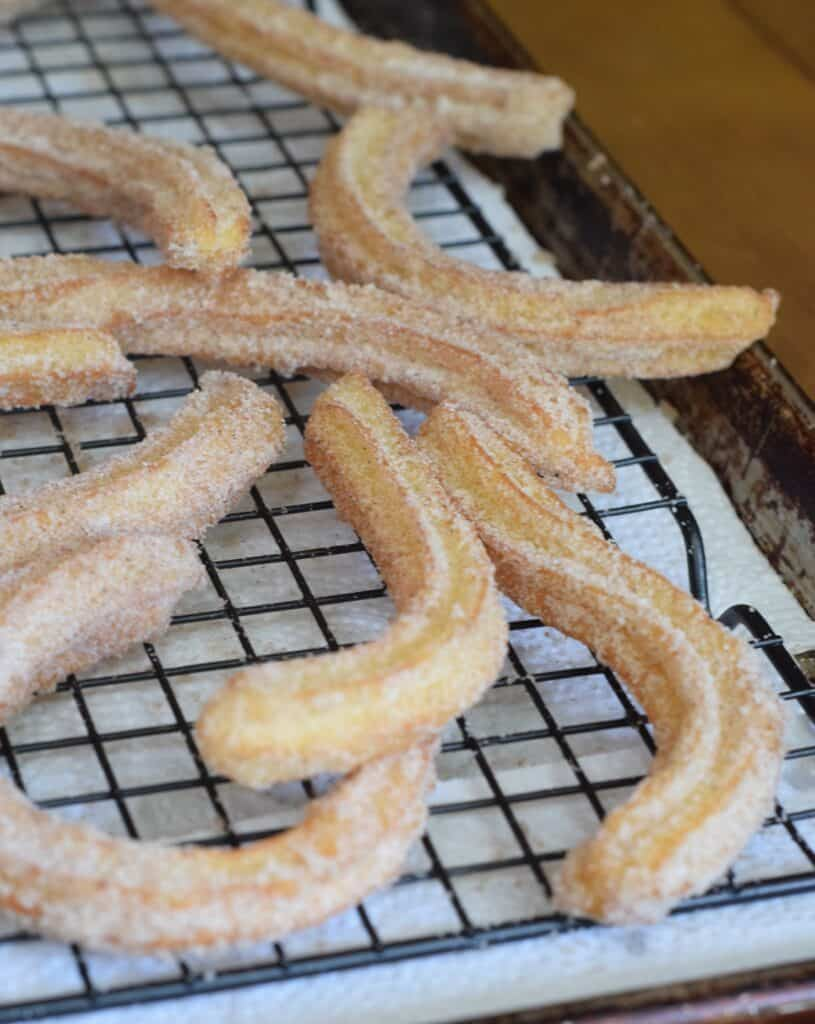 Churros cooling on a wire rack over parchment paper