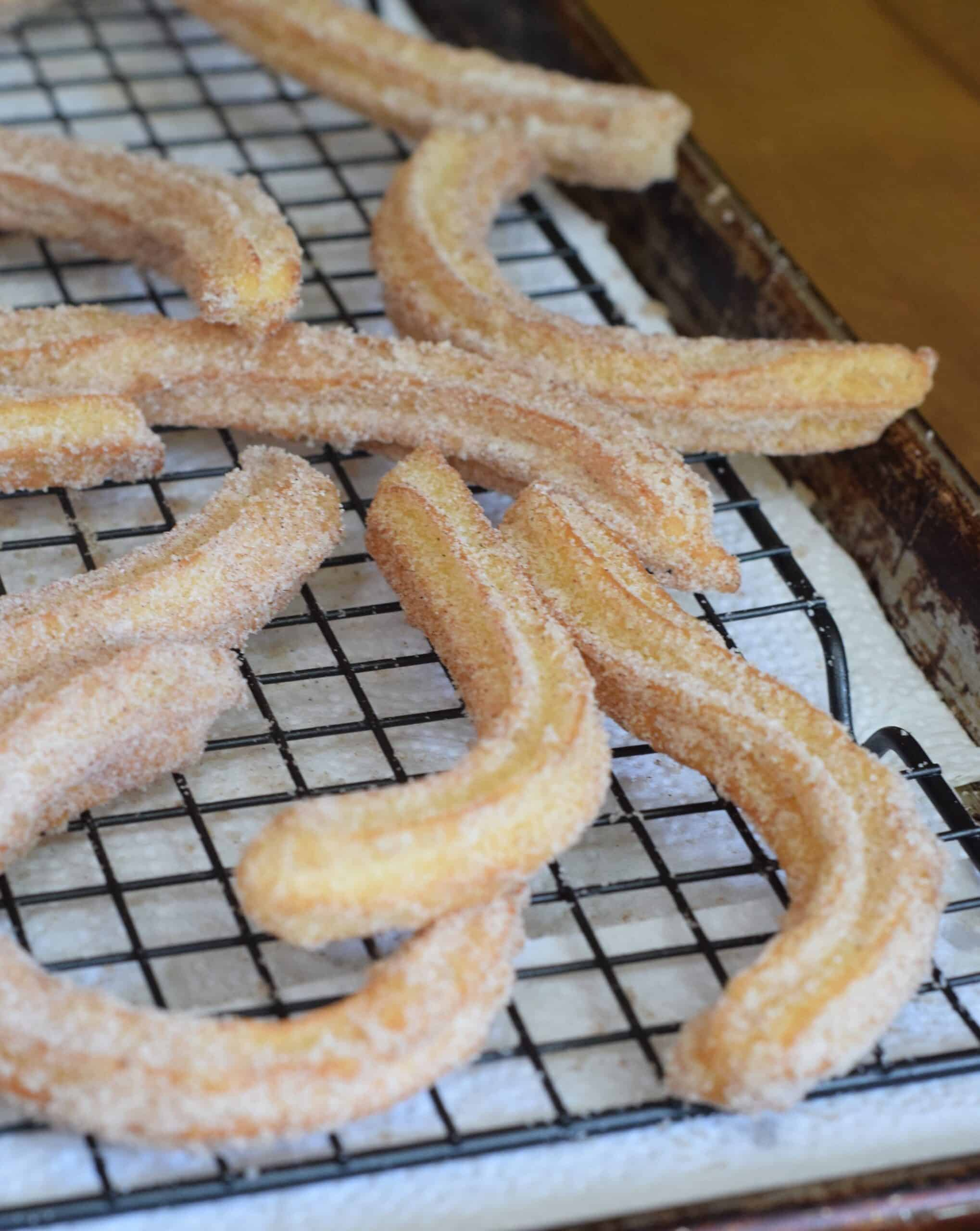 Churros cooking on a wire rack
