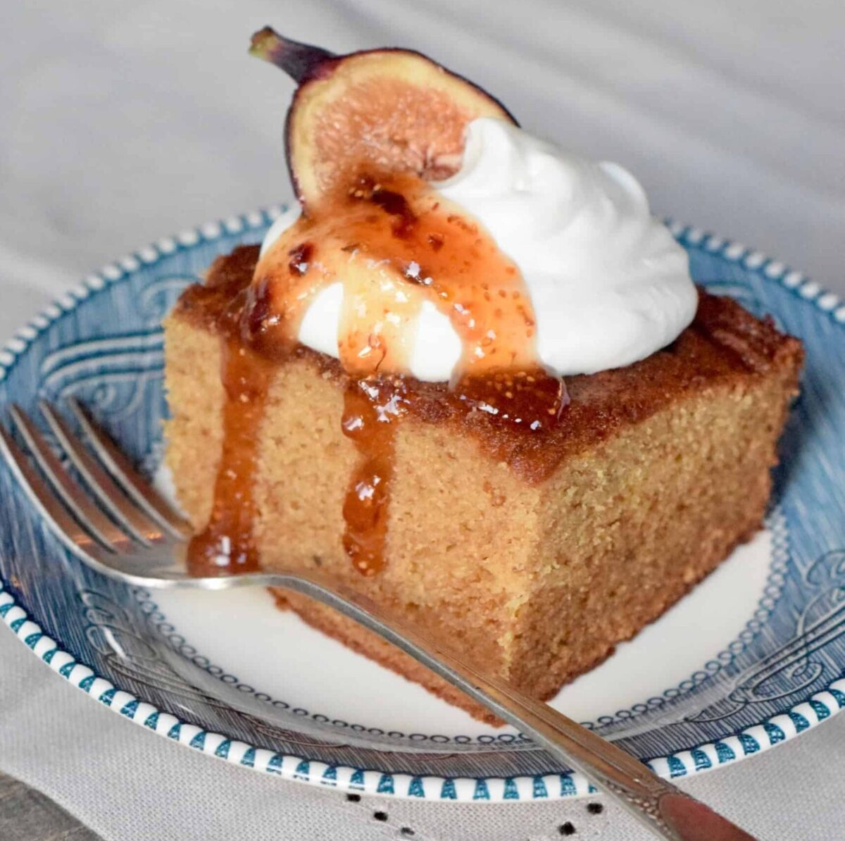 Square piece of Fig Jam Cake topped with dollop whipped cream, Fig and Lemon Preserves and a fig half