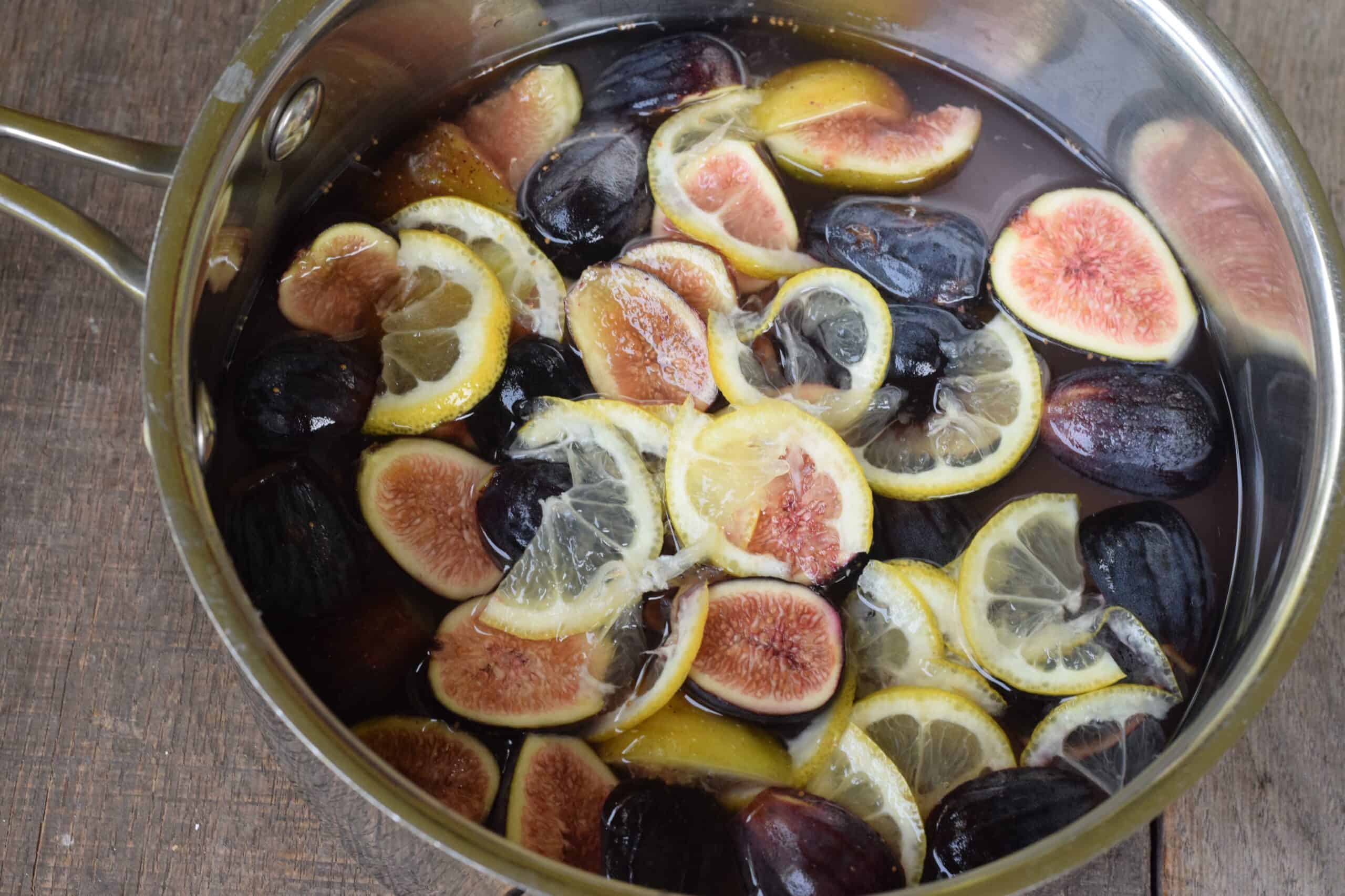 fig halves and lemon slices steeping in a saucepan of water