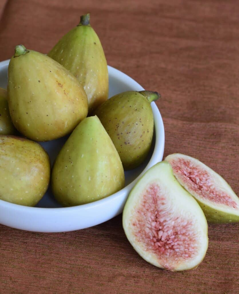 White bowl of green figs with one cut in half