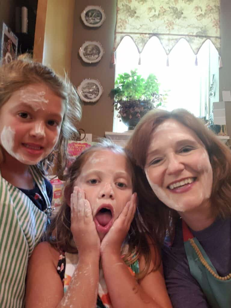 Kathleen Phillips with two girls helping in the kitchen with flour on their faces.