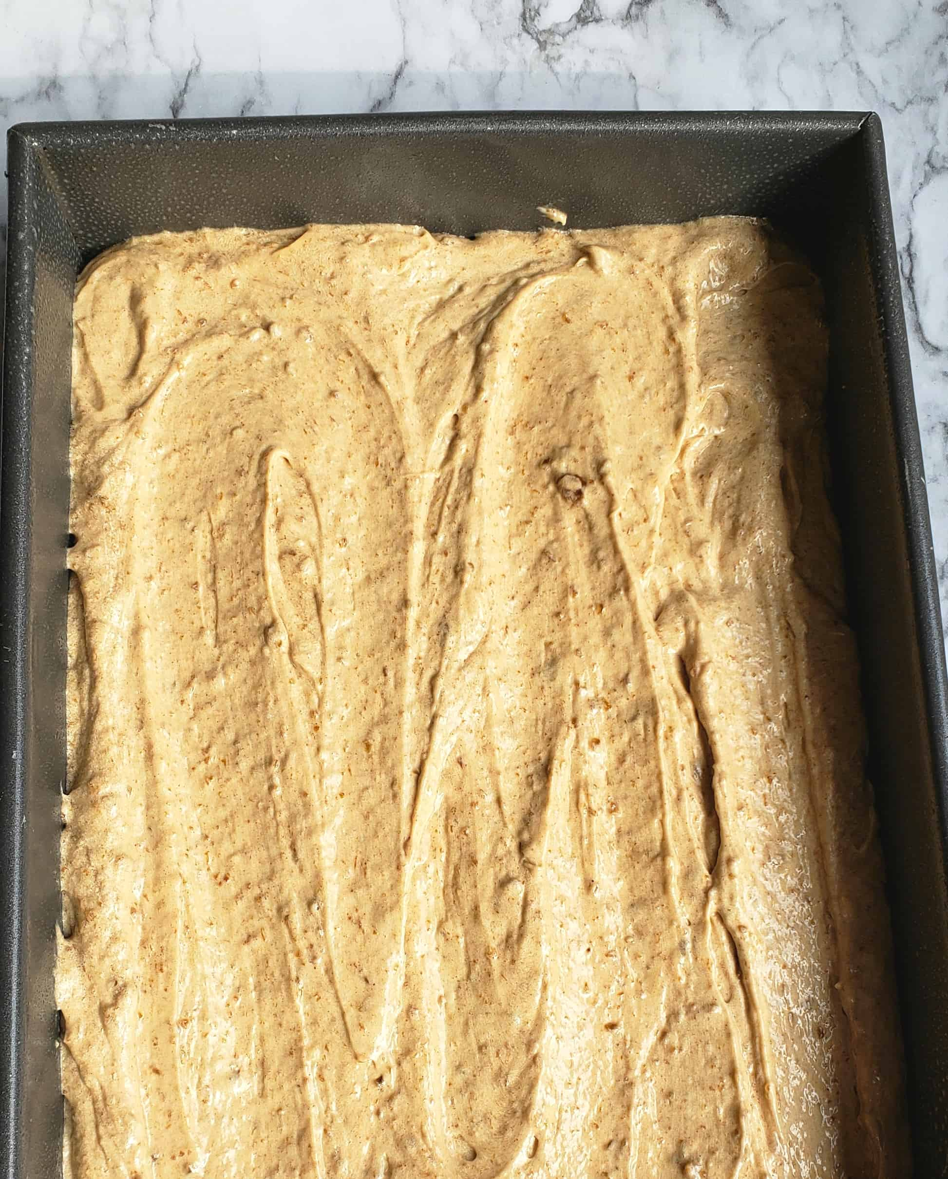 Fig jam cake batter spread in a baking pan
