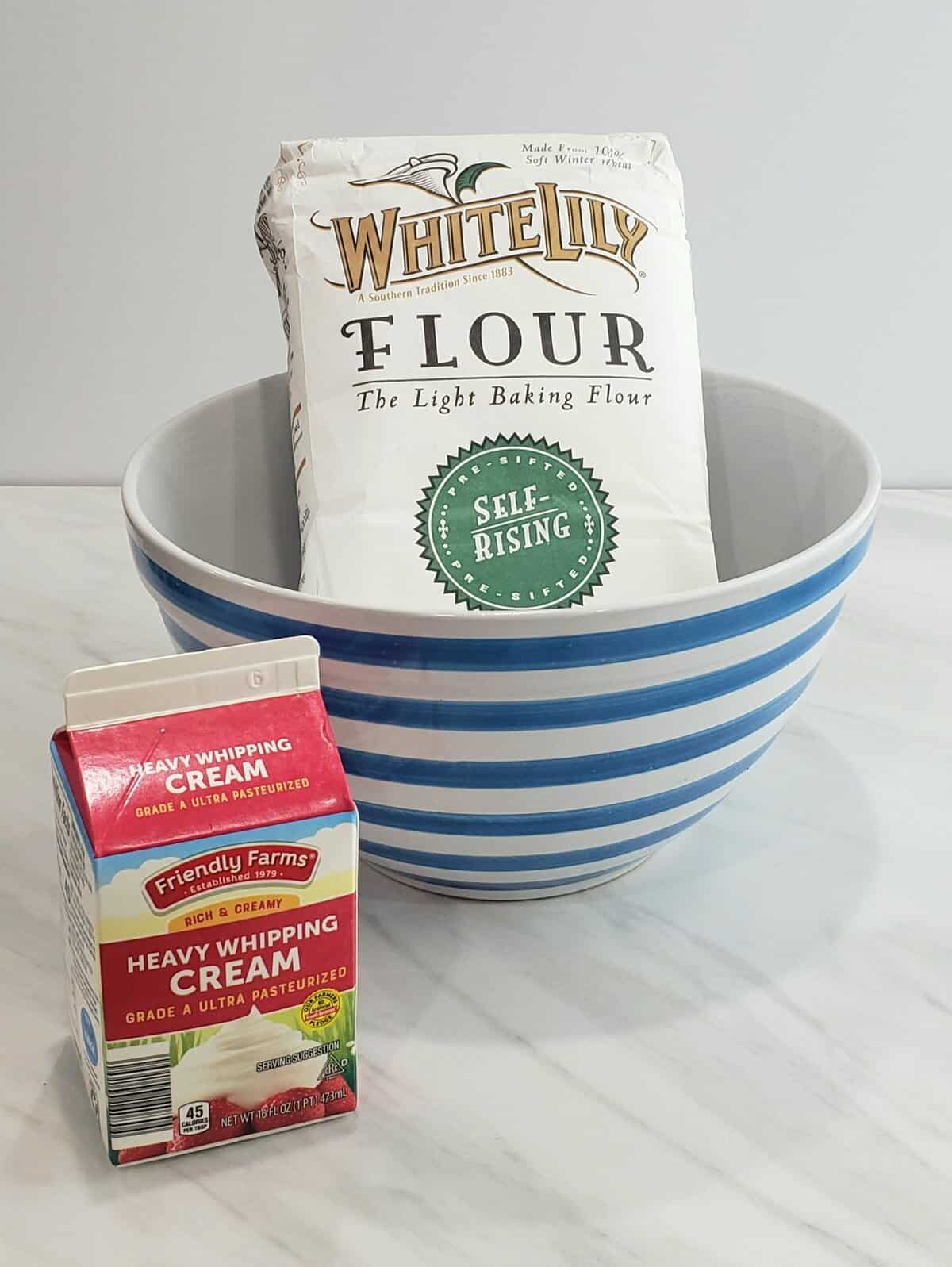 a bag of White Lily flour in a blue striped bowl with a quart of heavy whipping cream next to it