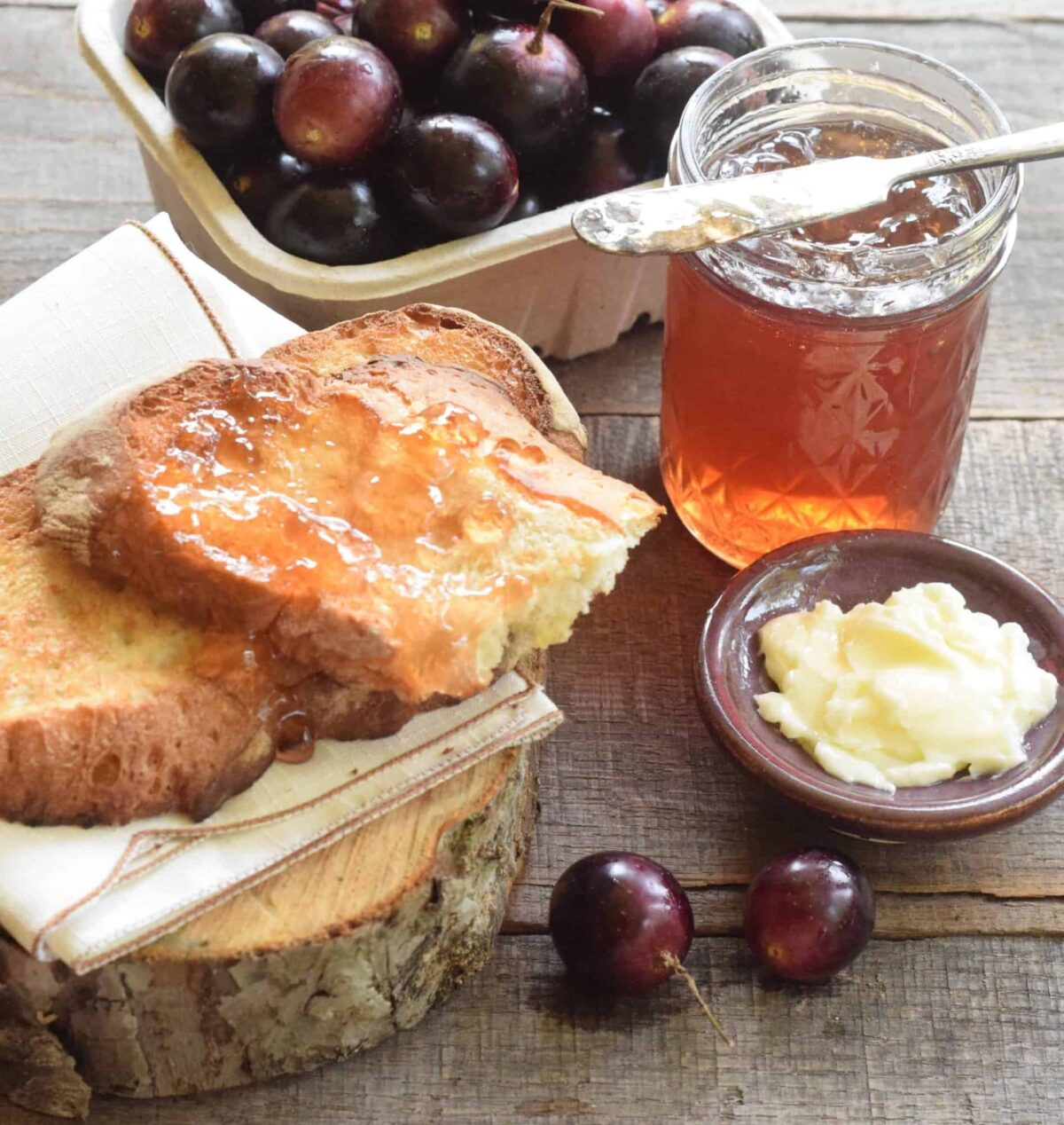 pint of muscadine grapes, jar of scuppernong jelly with knife resting on it, buttered slices of bread with jelly on a napkin on a slice of wood, butter in a ceramic plate