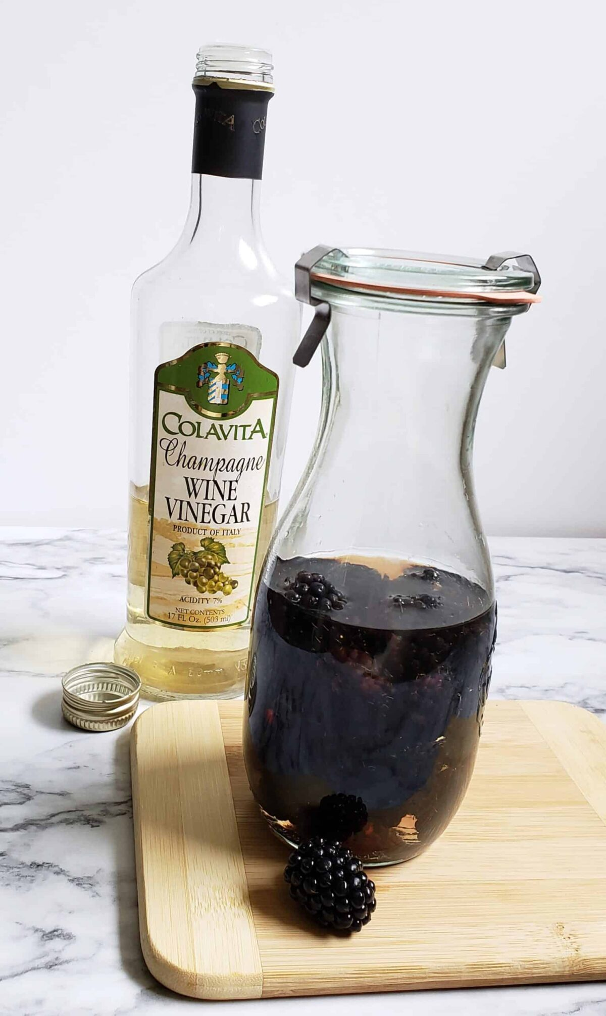 Weck jar of vinegar with blackberries in it. One berry on a cutting board. Champagne wine vinegar in bottle in background
