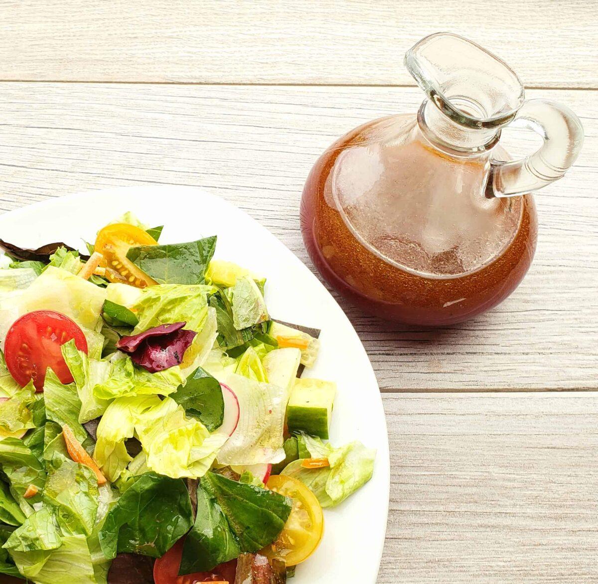 Black Raspberry Vinaigrette in a glass cruet, a tossed salad from overhead view