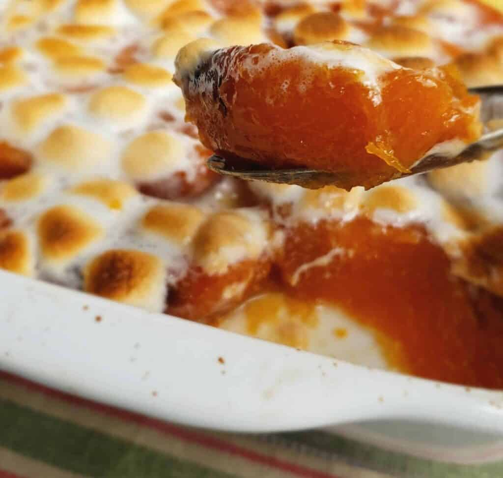 Broiled marshmallows top candied sweet potatoes with a spoonful lifted from the casserole dish
