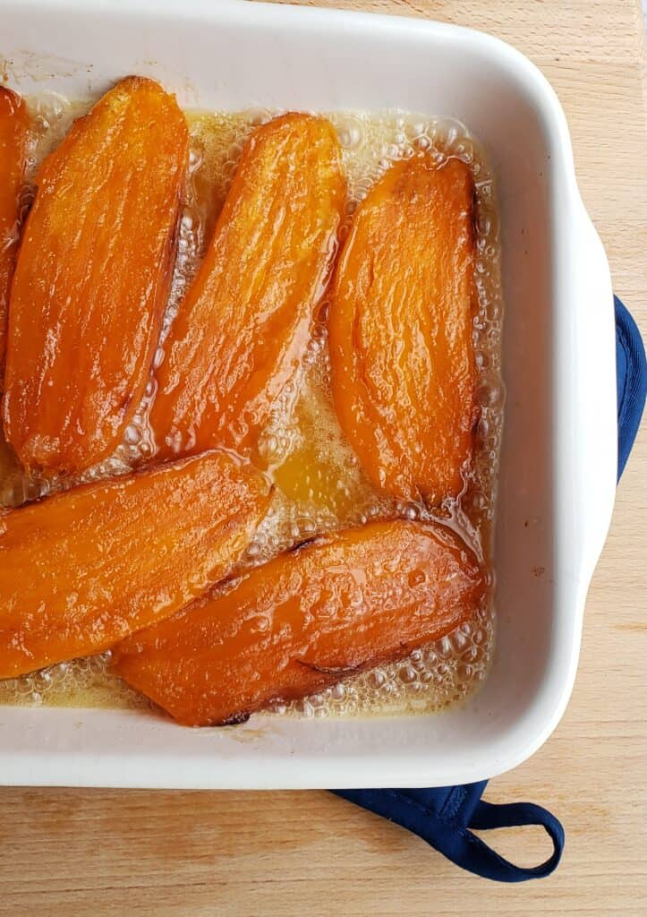Sweet Potatoes are roasted first, then candied in the oven in a white casserole dish on a blue pot holder.